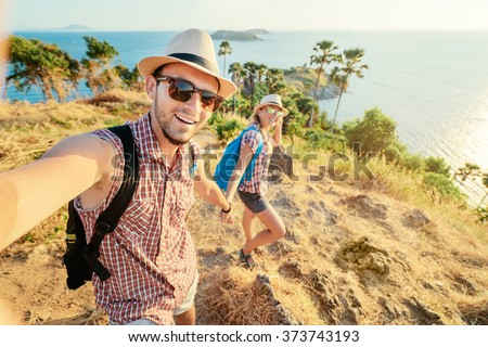 We love traveling and trekking! Adventure Selfie. Caucasian young loving couple taking selfie while they walking on mountains near the sea.