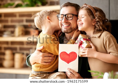 We love you, dad. Young happy father getting congratulations on Fathers Day from two excited kids at home, son and daughter, smiling children giving daddy handmade postcard and wrapped gift box