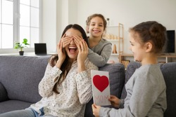 We love you, mommy. Excited young woman receiving present from kids. Little children wishing mother Happy Mother's Day. Two cute twin sisters cover mom's eyes as they give her handmade greeting card