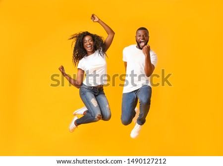 We made it. Joyful Afro Couple Jumping Up And Down, guy clenching his fist, yellow studio background