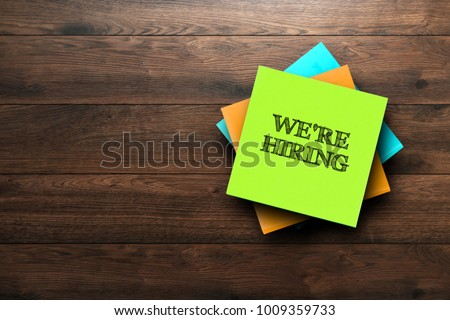 We're Hiring, the phrase is written on multi-colored stickers, on a brown wooden background. Business concept, strategy, plan, planning.