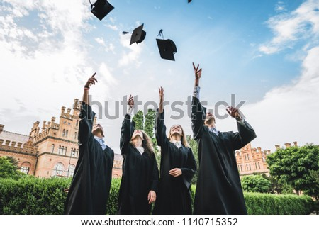 We\'ve finally graduated!Graduates near university are throwing up hats in the air.