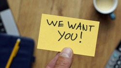 We want you written on a card with hand at a workingplace in a business situation