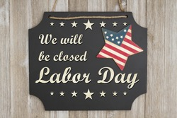 We will be closed Labor Day text on a chalkboard with patriotic USA red and blue star on weathered wood