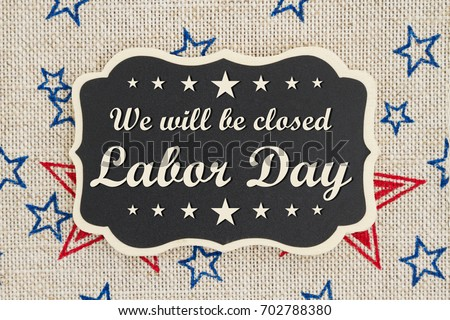 We will be closed Labor Day text on a chalkboard with patriotic USA red and blue stars on burlap #702788380