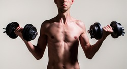 Weak man lift a weight, dumbbells, biceps, muscle, fitness. Nerd maleraising a dumbbell. Man holding dumbbell in hand. Skinny guy hold dumbbells up in hands. A thin man in sports with dumbbells.