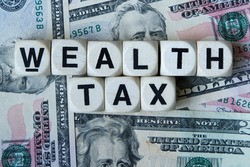Wealth tax signage with a background of American dollars.