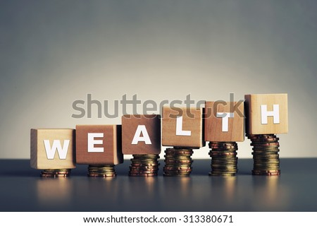 wealth text written on wooden block with stacked coins on grey background