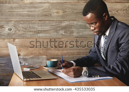Wealthy and serious dark-skinned businessman with laptop checking report in cafe with a cup of coffee. Young African entrepreneur is focused on work issues and signing papers for business deals.