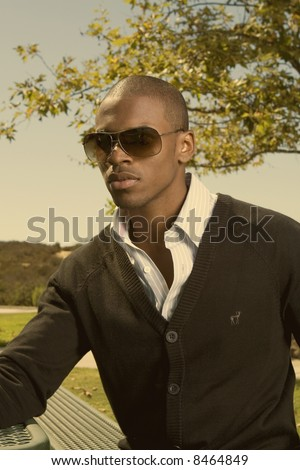 wealthy young black man sitting in a park with sun glasses