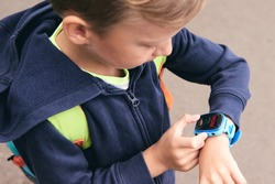Wearable kids baby smart watch calls mom and location tracking with touch screen and voice service, blue multicolored electronic gadget with rubber wristband for children. Close up boy with copy space