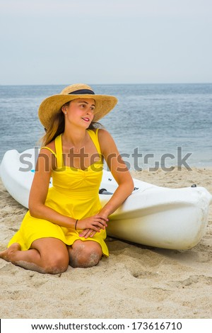 stock-photo-wearing-a-bright-yellow-sundress-a-straw-hat-a-pretty-girl-is-kneeling-down-on-the-beach-by-a-173616710.jpg