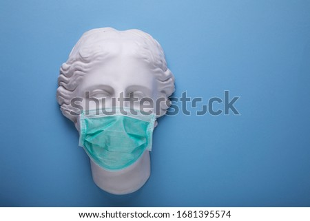 Wearing a single use medical protection mask, greek gypsum statue with surgical mask on blue background