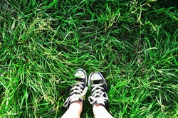 Wearing black canvas shoes in the grass