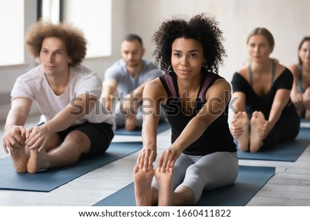 Wearing comfy stylish grey black color activewear group of people working out performing Seated Forward Bend exercise. Mixed-race woman and associates gather together for yoga training at sport club