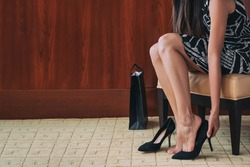 Wearing high heels shoes foot pain woman. Feet care health problems with pointy toes, arch support, insoles. Shopping footwear businesswoman trying on new black suede stilettos in store.
