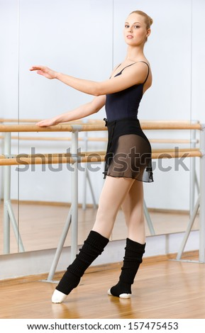 Wearing leotard and warmers female ballet dancer dances near barre and mirrors in dancing hall