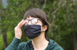 Wearing Mask and Glasses Outdoors and Cleaning Condensation Fog using Finger. Portrait of Young Woman Wearing Homemade Protective hygienic face medical mask to prevent 2019-nCoV, Covid, Coronavirus.