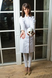 Wearing medical overall physician gives pills and cranium