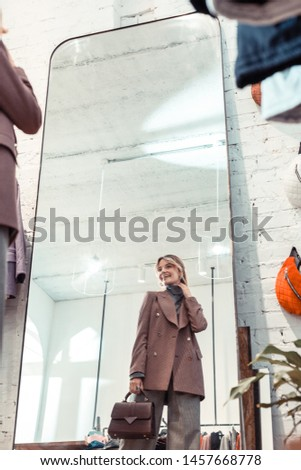 Wearing stylish jacket. Blonde-haired beautiful woman wearing stylish jacket standing in clothing boutique