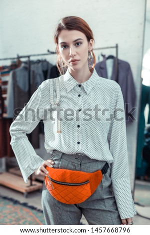 Wearing stylish trousers. Owner of fashion boutique wearing stylish trousers and blouse with bright waist bag
