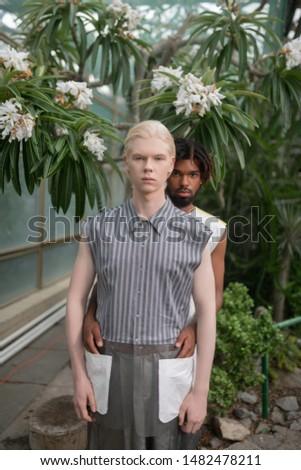 Wearing unusual jacket. Blonde-haired man wearing unusual jacket standing in front of his friend
