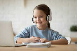 Wearing wireless headphones makes videocall little beautiful schoolgirl using web cam and notebook learning school subject distantly due quarantine or home schooling. Remote self-education concept