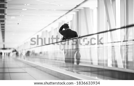 Weary businessman pedestrian walking alone on moving walkway inside a modern terminal link. Black and white. Stock photo ©
