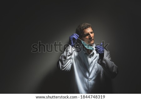 Weary Doctor Removing PPE COVID Face Mask Stock photo ©