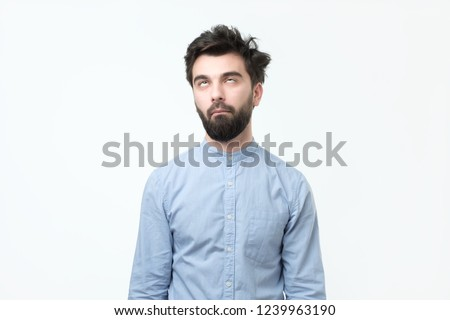 Weary hispanic man in blue shirt rolling his eyes up. He is exhausted with work or tired of listening his wife chatting.