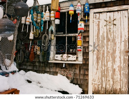Weather beaten and worn doorway of a lobsterman's fishing shack with colorful buoys