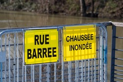Weather - Flood warnings in France. Two yellow warning signs fixed on a metal barrier and written in French: