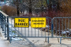 Weather - Flood warnings in France. Two yellow warning signs fixed on a metal fence and written in French: