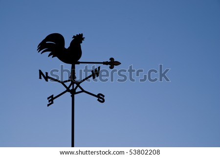 Weather vane silhouetted against a clear blue sky