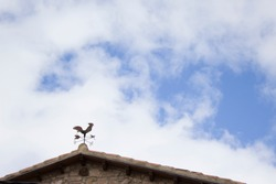 Weathercock on roof and blue sky