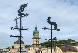 weathercocks in the form of a dragon and a rooster on the background of the old ukrainian city Lviv