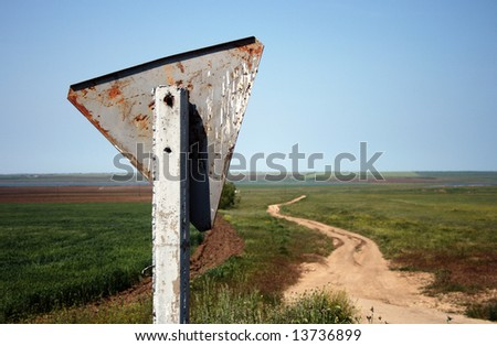 Weathered and crooked road sign in the countryside. Crimea, Ukraine.