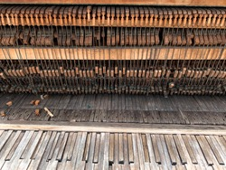 Weathered and eroding old wooden musical piano in disrepair with broken strings and keys sits outdoors in the rain and weather elements in need of repair, restoration and retune. Mitcham, England