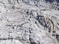 Weathered and etched natural marble surface with fine and big cracks. Gray white striped marble rock weathered by rain and wind. Abandoned marble quarry. Changes in the shape of a stone under the inf