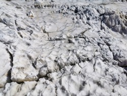 Weathered and etched natural marble surface with fine and big cracks. Gray white striped marble rock weathered by rain. Changes in the shape of a stone under the influence of the natural phenomena.