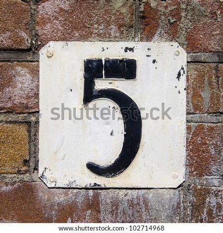 weathered and flaking house number five on a brick wall