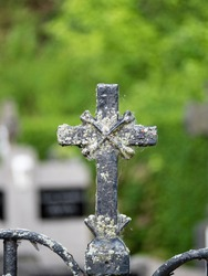 Weathered and old iron cross on a fence near a cemetery