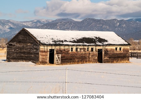 Weathered barn on a ranch in Montana in the winter with a beautiful mountain view