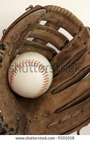 weathered baseball mit and baseball - stock photo