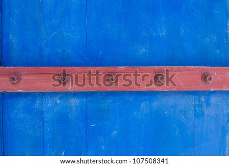 Weathered blue wooden door texture with rusty forged nail heads