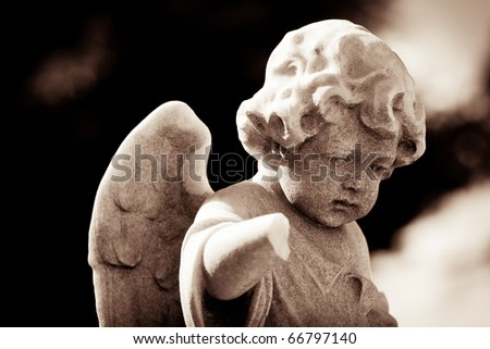 Weathered child angel statue in sepia tones