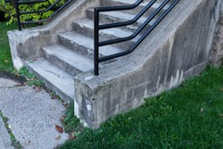 Weathered concrete stairs with heavy black pipe railing, grassy yard and concrete walkway, horizontal aspect