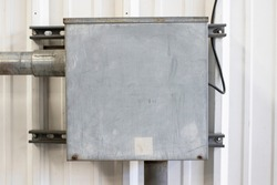 Weathered electrical box mounted on a metal wall inside a factory