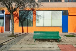 weathered green wood bench in front of an orange wall with blue door and window frames