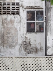 weathered grunge roadside concrete apartment wall with windows frame cover with mosquito net street view authentic shot of usual urban downtown scene in BANGKOK